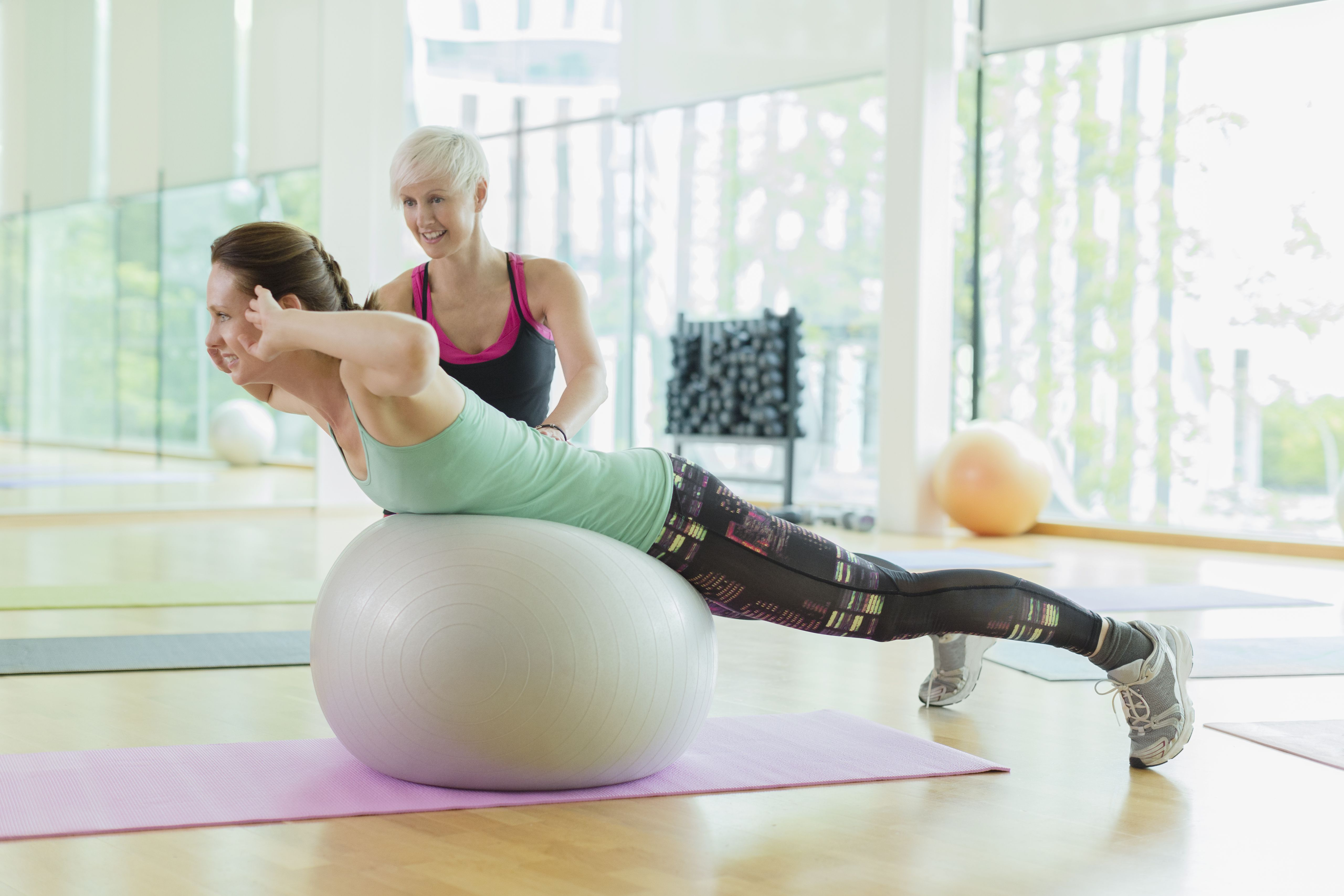 Personal trainer guiding woman doing back extensions on fitness ball
