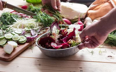 Man tossing a colorful salad with his hands