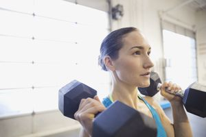 Woman lifting weights, two dumbbells at shoulder height