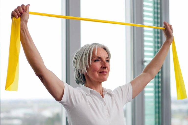 Older woman stretching in gym
