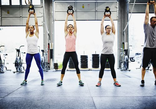 Three women (left) and one man (right) swing kettlebells overhead in a CrossFit gym