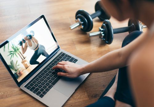 A woman watching a workout video on her laptop.