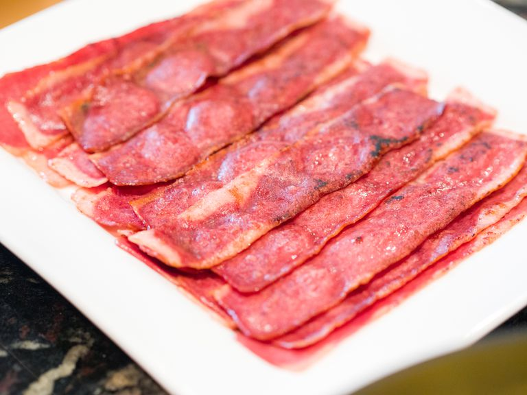 A close up photograph of several sizzling hot turkey bacon slices or pieces on a white serving plate on a kitchen counter ready to eat for breakfast.