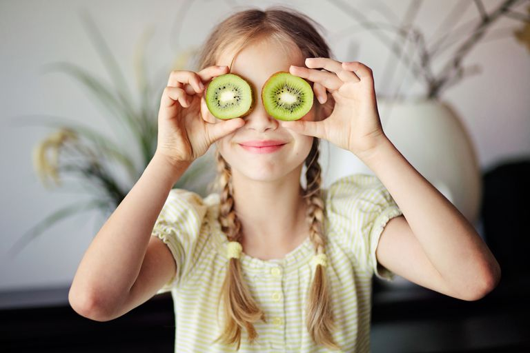 Girl holding two sliced kiwis up to her eyes