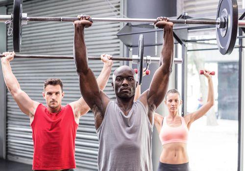 Tres atletas realizan una barra de pesas sobre el hombro.