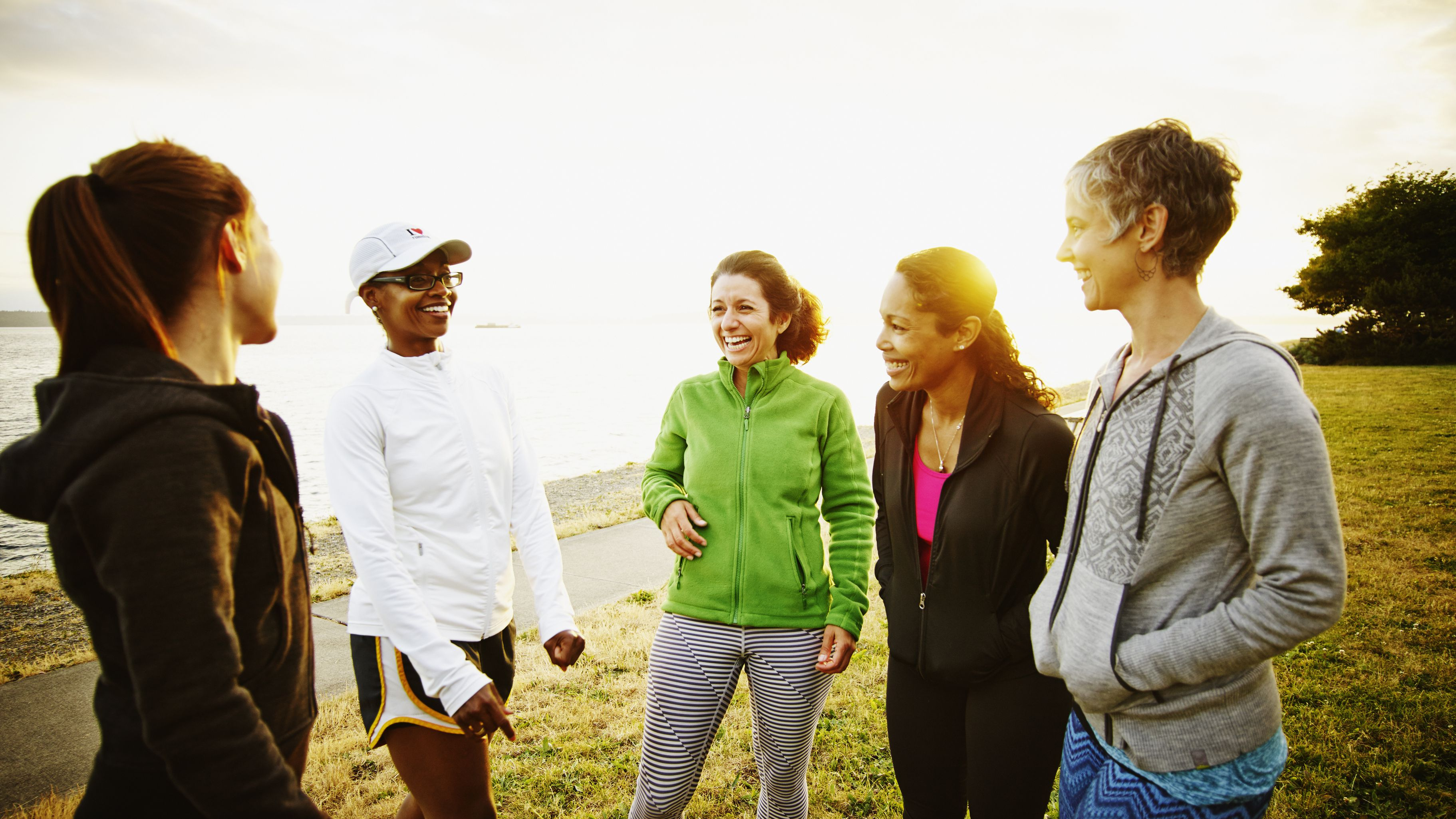 female friends laughing to her after run in park ad05f9b58f22ecf062e