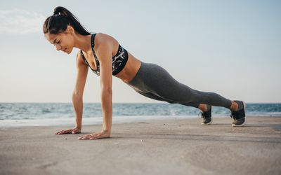 woman performing plank on beach
