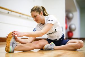 Woman stretching leg muscles in a gym