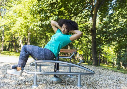 mujer haciendo abdominales en el parque