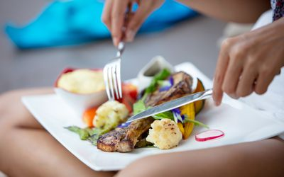 woman eating steak and vegetables