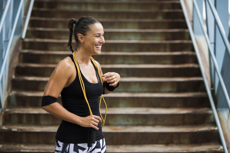 Woman smiling and sweating with jump rope around her neck