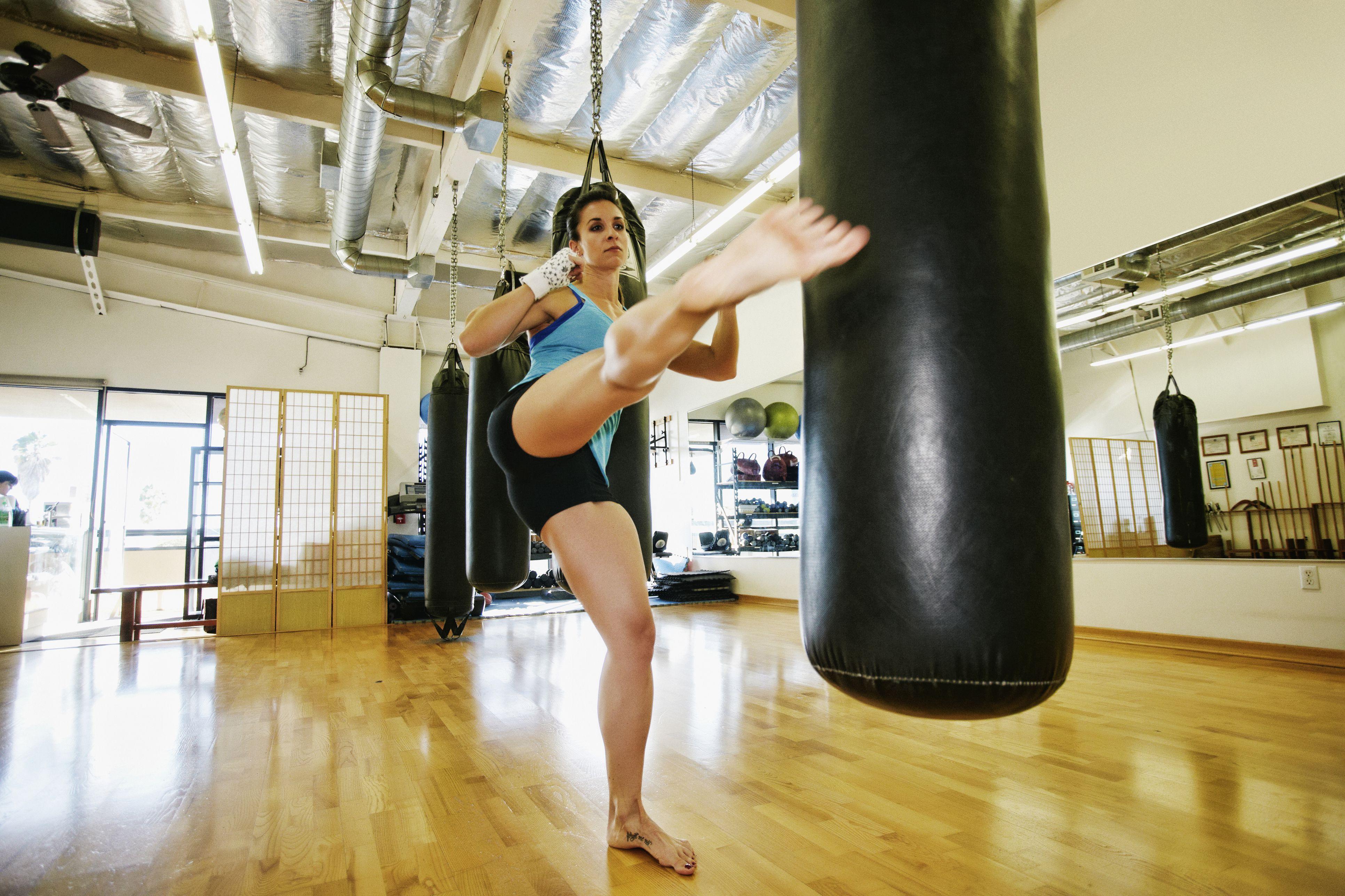 Mujer de raza mixta pateando un saco pesado en el gimnasio