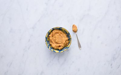 Miso in a yellow and blue bowl with a spoon.