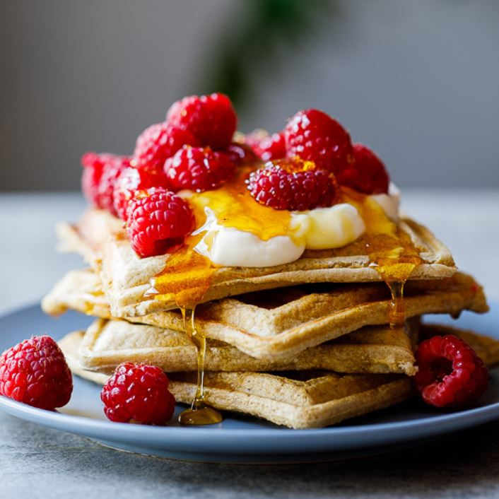 Waffles topped with raspberries and bananas