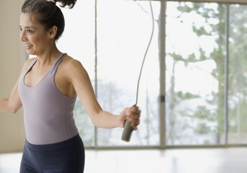 Hispanic woman jumping rope during workout