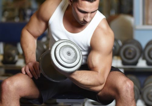 Man with large muscles, seated, lifting a weight