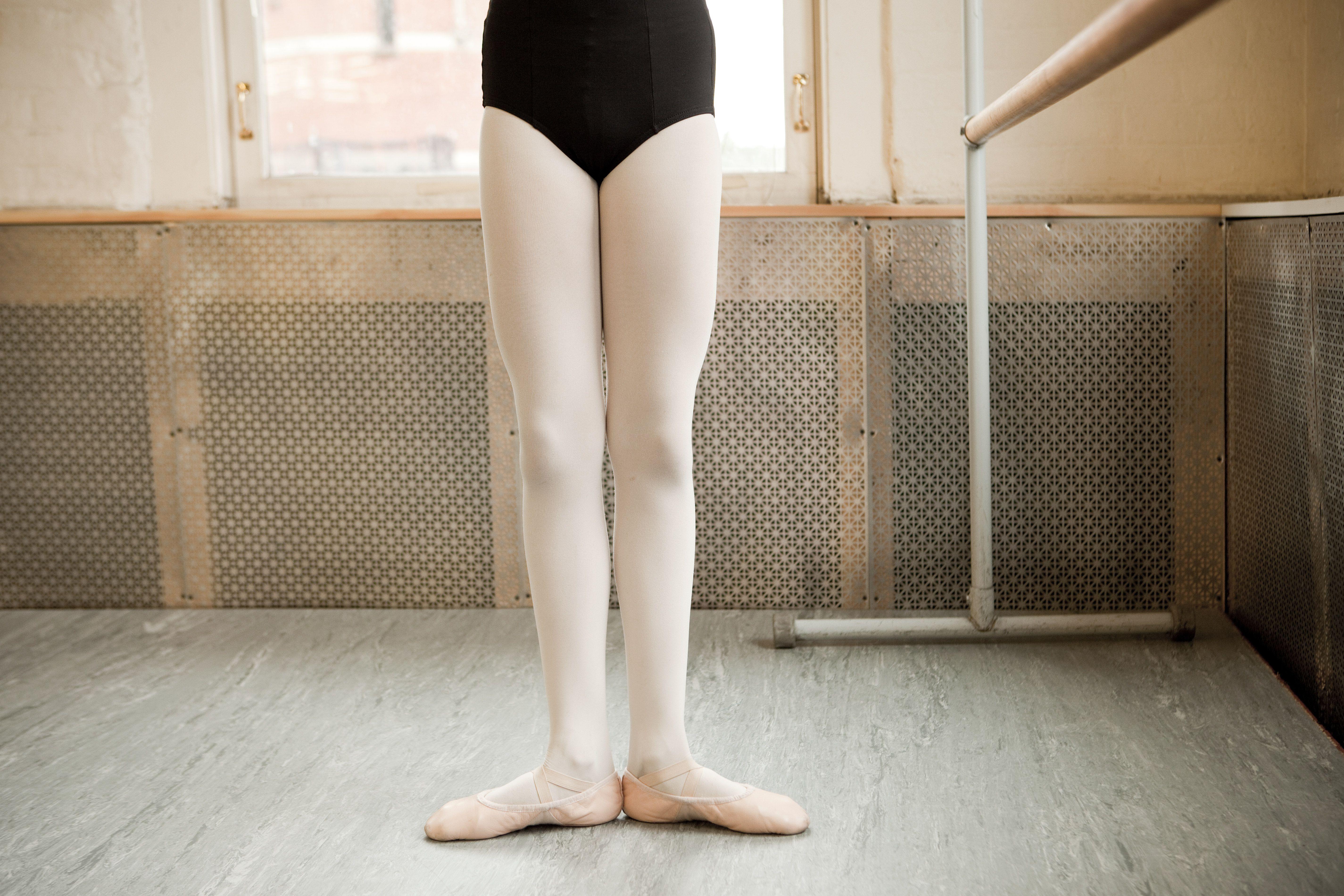 Piernas de una bailarina con pies en primera posición