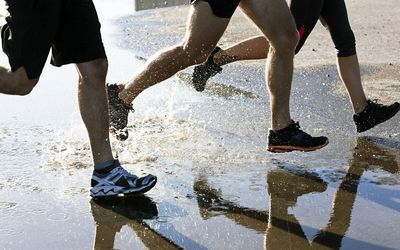 People running on puddles in concrete