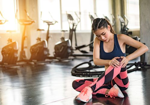 mujer joven con rodilla mientras está sentado en el piso en el gimnasio