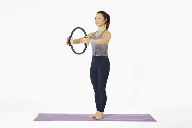 Woman standing on yoga mat using Pilates Magic Circle