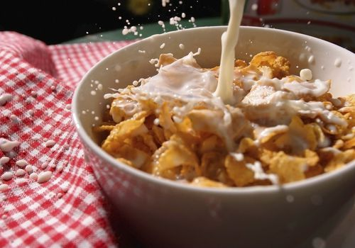 Pouring milk on a bowl of cornflakes