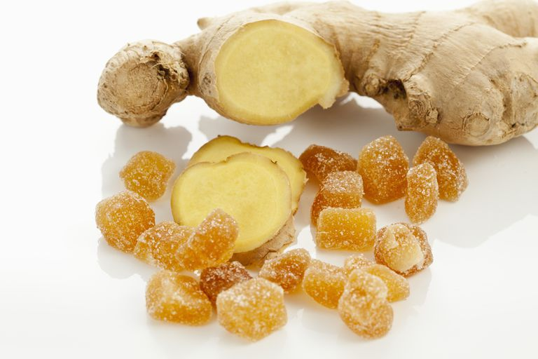 Sliced ginger and pieces of candied ginger on white background, close up