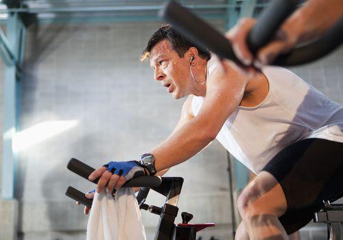 Hombre hispano en bicicletas estáticas en gimnasio