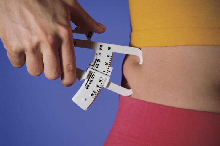 Woman measuring percentage of body fat on waist