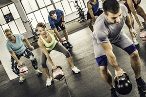Fitness group doing kettlebell lifts