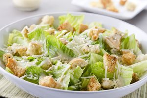 Bowl of Caesar salad with gluten-free croutons and cheese