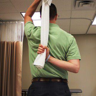 Use una toalla para llevar el brazo detrás de la espalda para estirar el hombro.