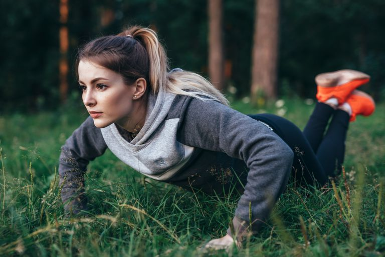 Young pretty blonde working out on grass in park doing knee push-ups