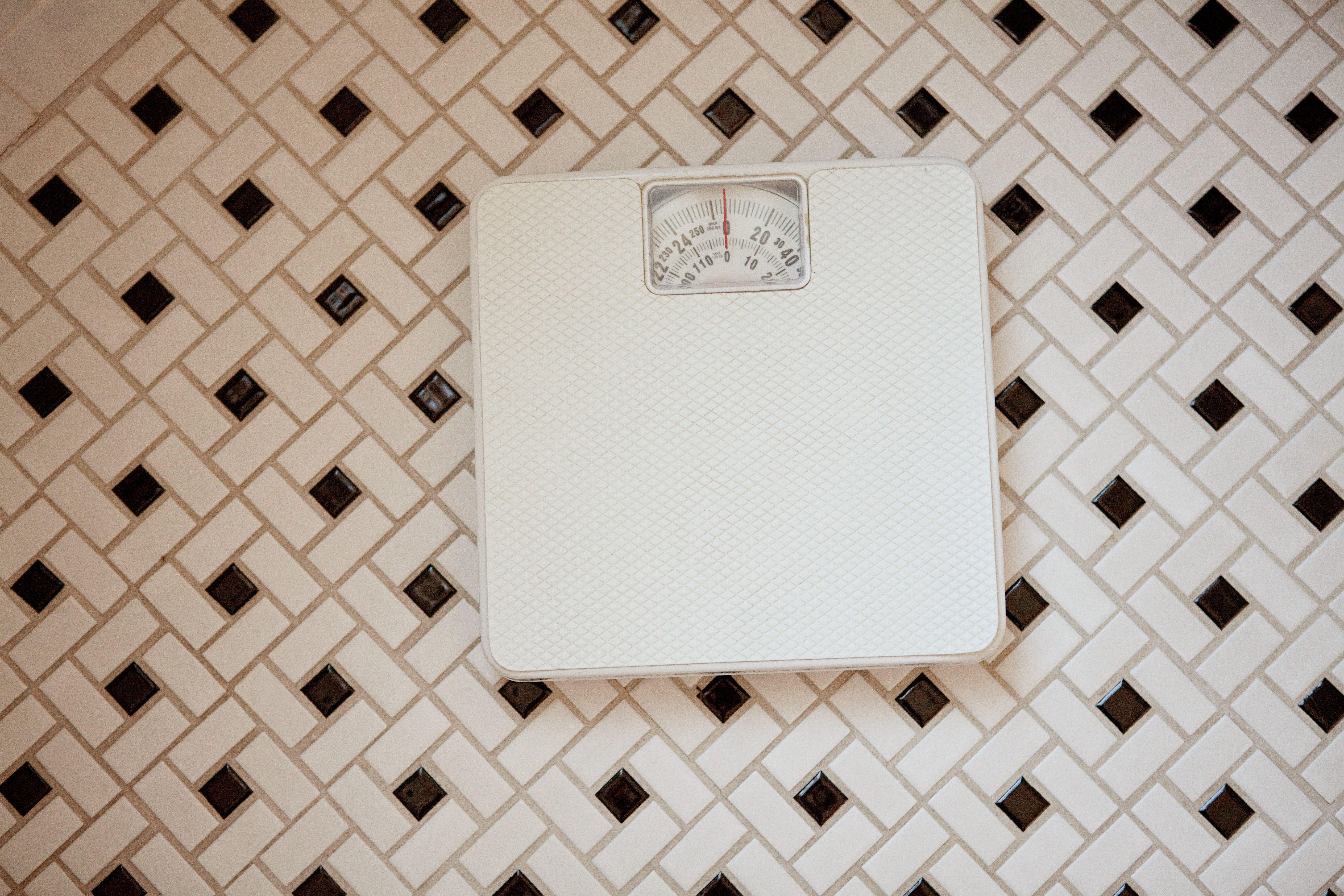 Básculas de baño sobre suelo de baldosas.