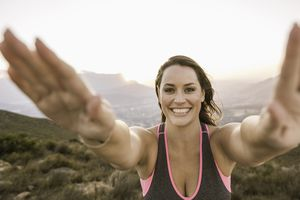 Plus size woman on mountain arms raised looking at camera smiling