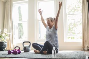 Smiling mature woman with hands raised doing yoga