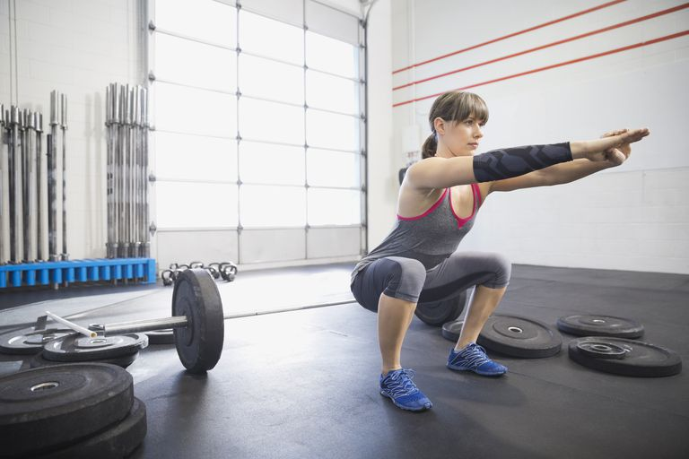 Woman warming up with squats in gym