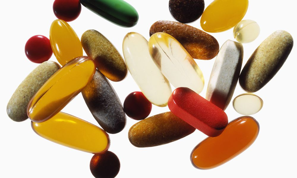 A group of various colorful supplement pills on a white background.