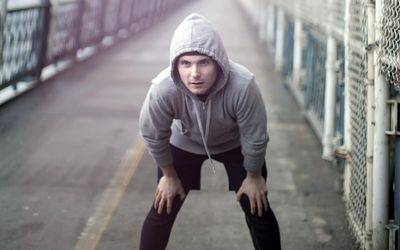 Runner with hand on knees on a running path