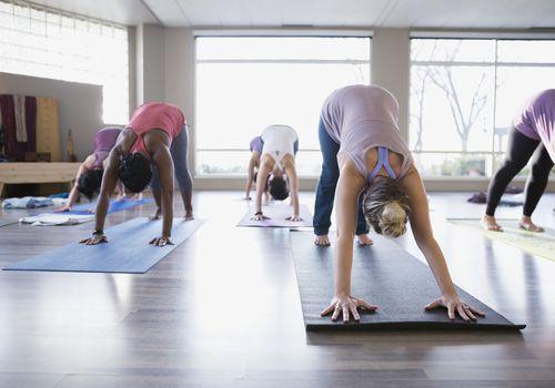 Mujeres practicando perro boca abajo en clase de yoga