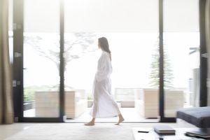 Woman in bathrobe walking through living room