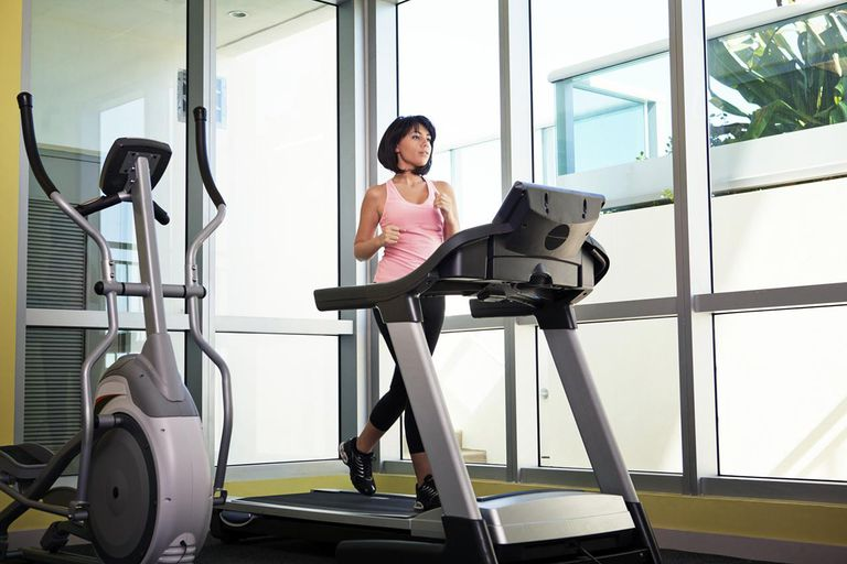 Woman running on a treadmill in a fitness center