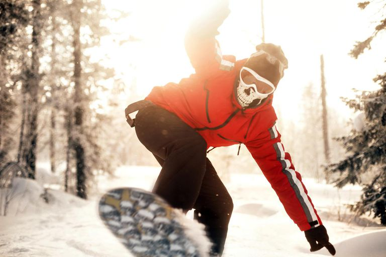 Snowboarder riding down slope lined with trees