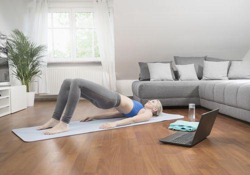 Mujer joven con laptop haciendo yoga en la estera del ejercicio en la sala de estar, Baviera, Alemania