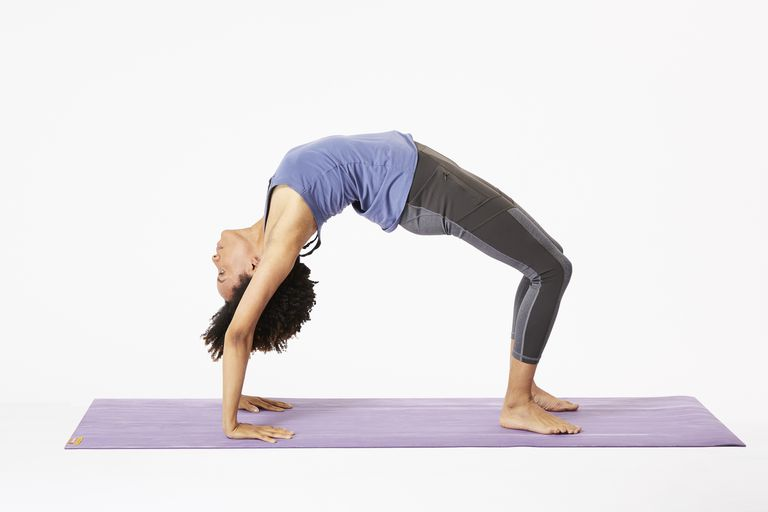 Woman on yoga mat doing wheel pose