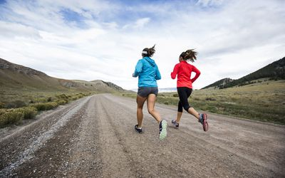 Two women running on dirt road