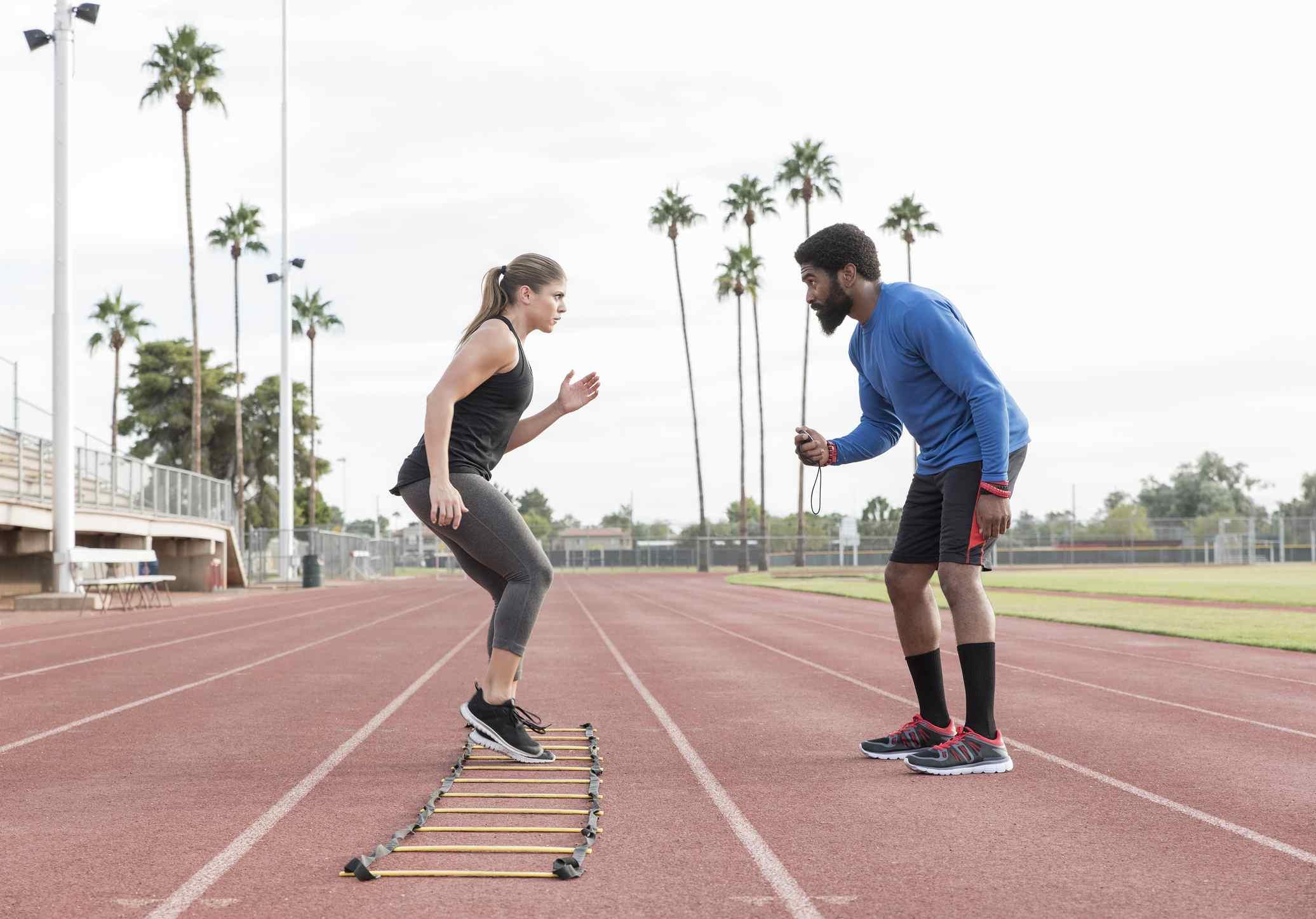 Mujer haciendo ejercicios de escalera con ayuda de entrenador masculino