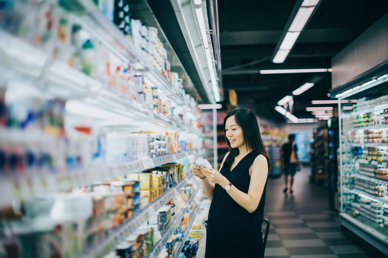 Woman looking at product's nutrition label in a grocery store aisle