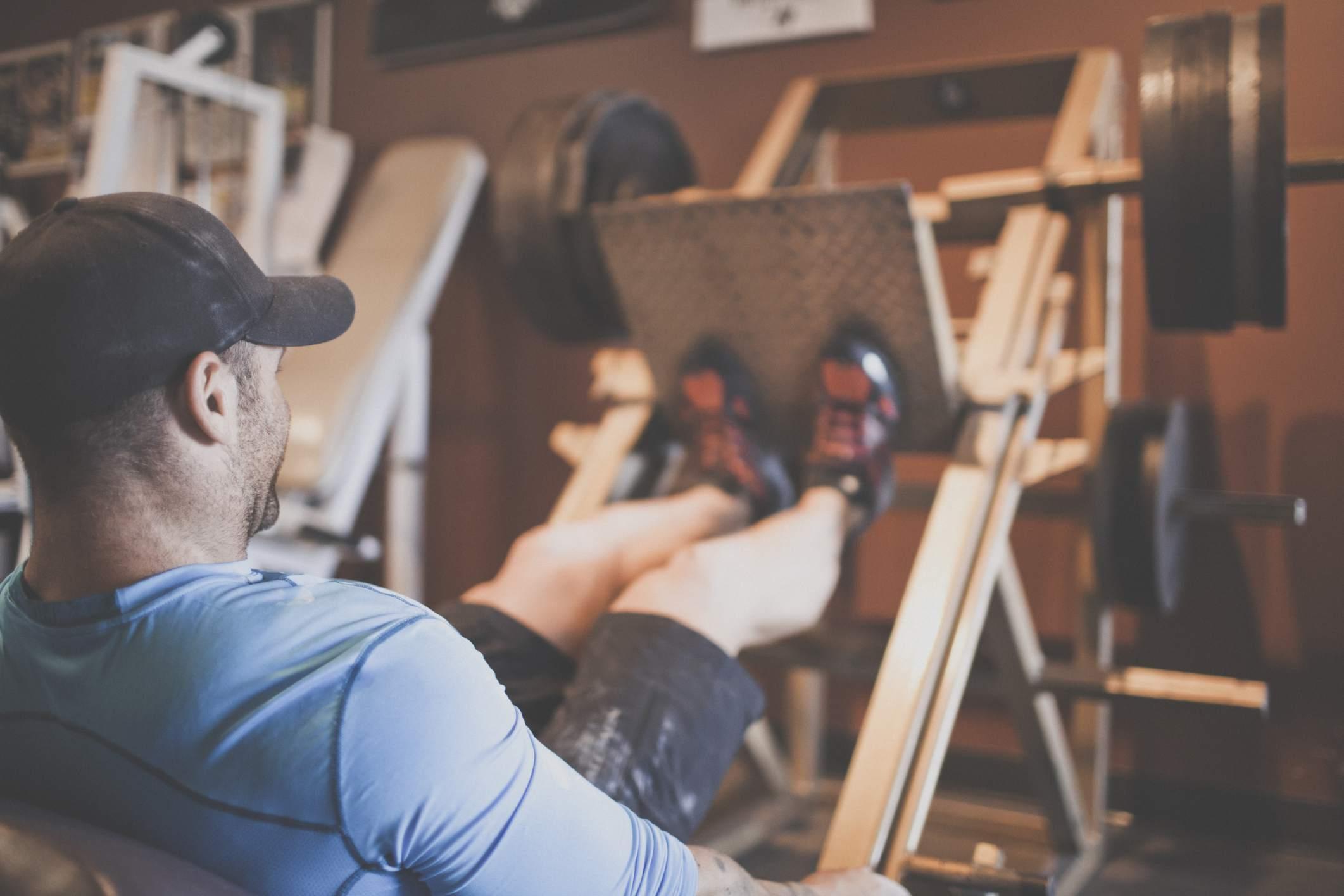 man using leg press in gym