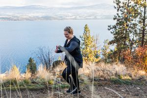 woman walking in the woods on a coastal mountain trail and checking watch