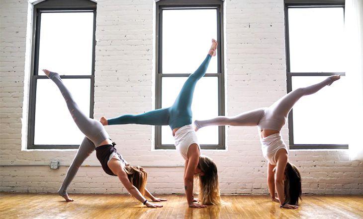 3 mujeres haciendo yoga frente a las ventanas